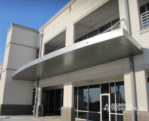 Showing an aluminum canopy protecting the entryway to a commercial structure.