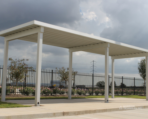 Showing an aluminum shade structure protecting a bus stop.