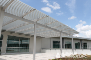 Showing an outdoor aluminum sun control structure near the entrance of a building.
